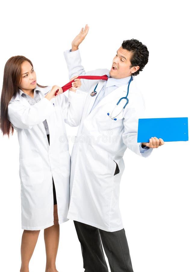 Сердитый женский доктор Assaulting Мужчина Коллега V стоковое изображение rf