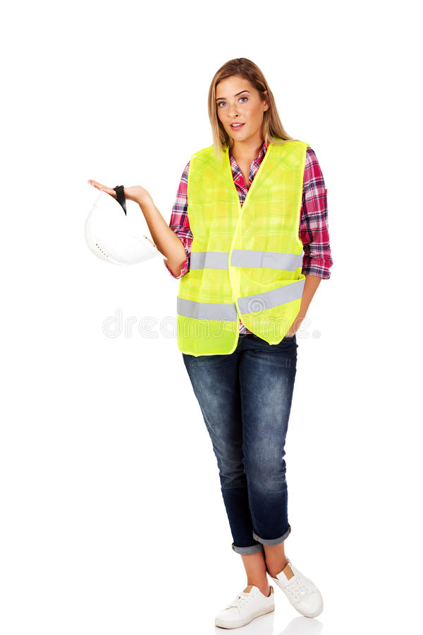 Сердитый женский построитель держа шлем стоковая фотография rf