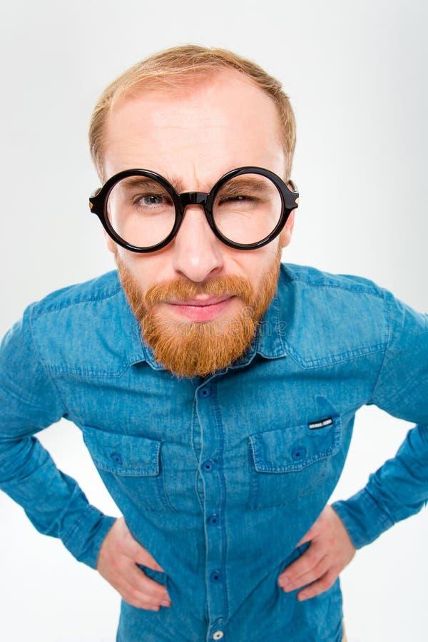 Сердитый забавный молодой человек с бородой в смешных круглых стеклах стоковая фотография