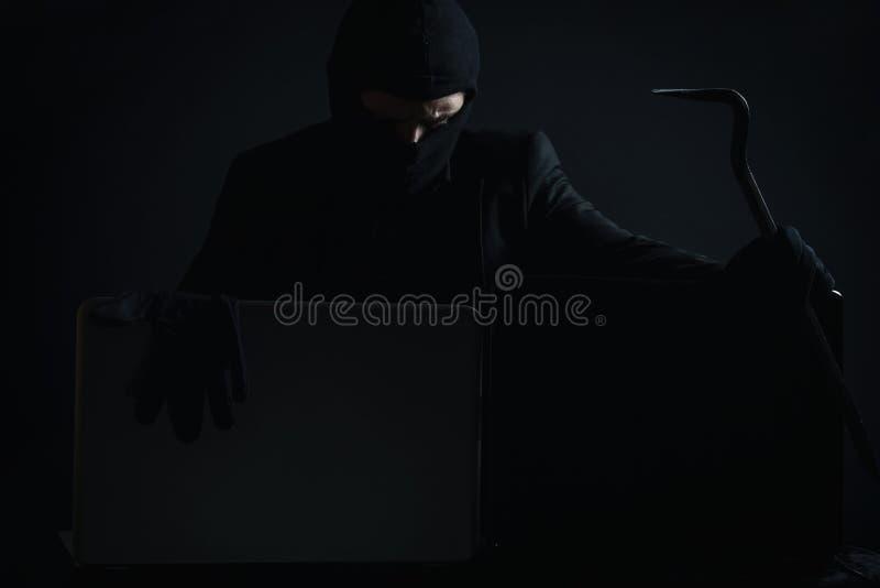 Сердитый компьютерный хакер в костюме крадя данные от компьтер-книжки с cro стоковое изображение rf
