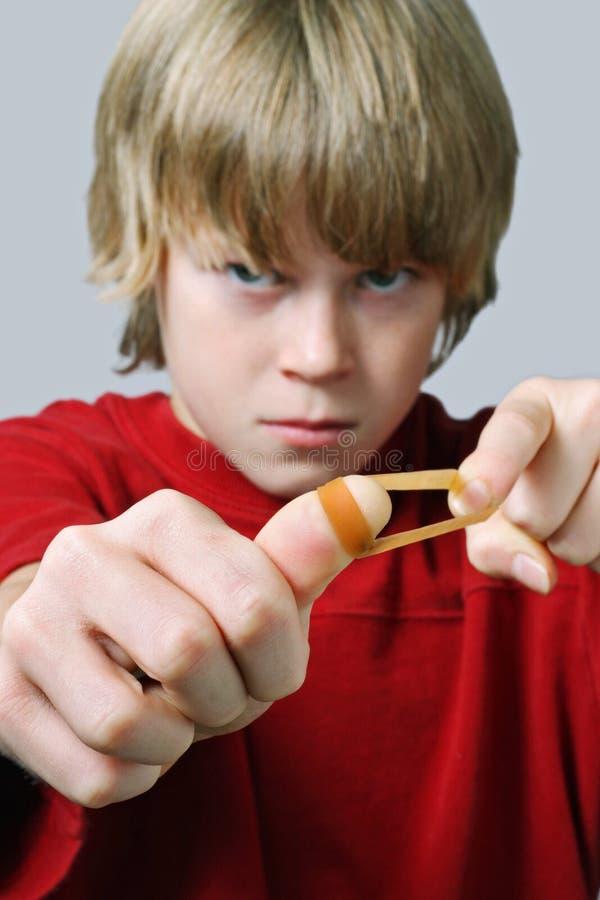 Сердитый мальчик направляя круглую резинку стоковые фото