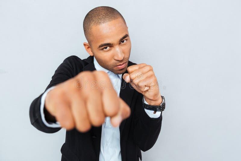Сердитый молодой бизнесмен стоя в положении боксера готовом для боя стоковая фотография
