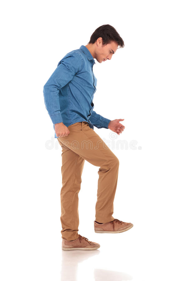 Сердитый молодой вскользь человек шагая на что-то стоковые изображения rf