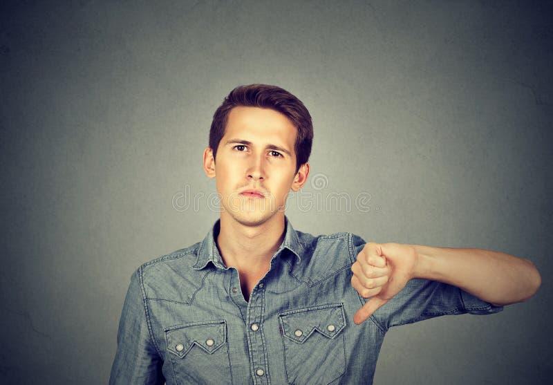 Сердитый молодой человек показывая большие пальцы руки вниз подписывает, в неутверждении стоковые фотографии rf