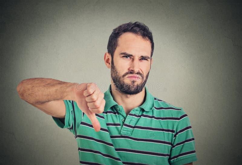 Сердитый, несчастный, молодой человек показывая большие пальцы руки вниз подписывает стоковое фото rf