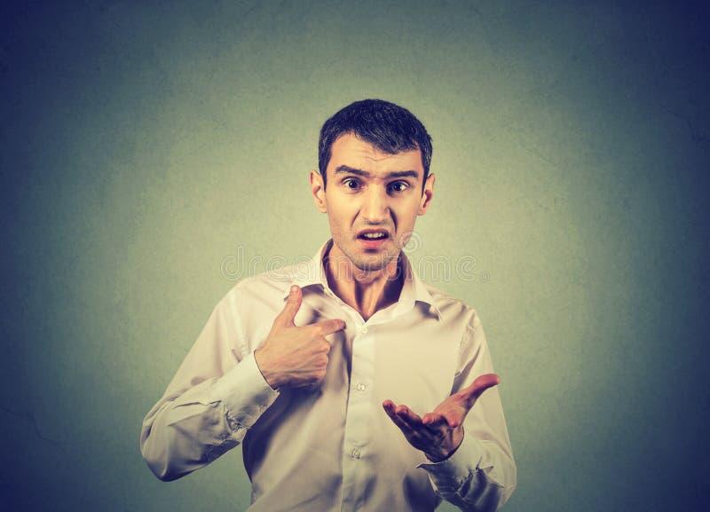 Сердитый парень указывая на себя спрашивая вам середину я, вы говоря к мне стоковое фото rf