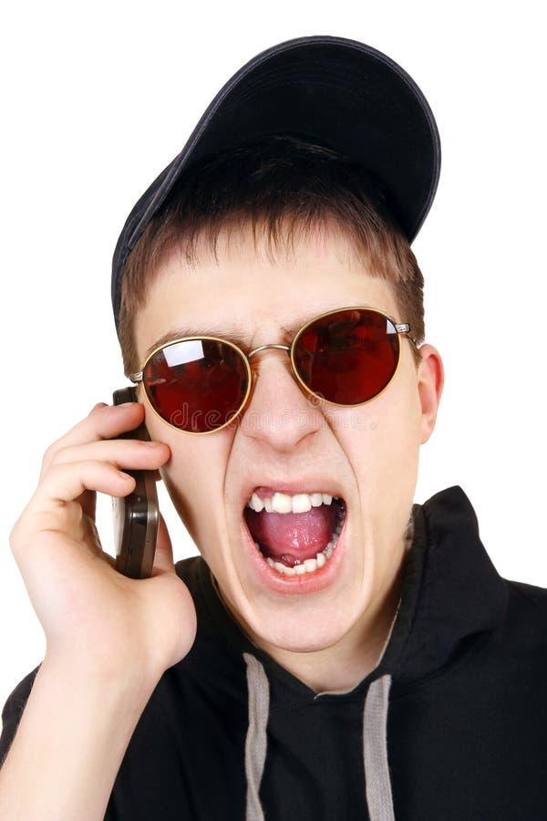 Сердитый подросток с мобильным телефоном стоковая фотография rf
