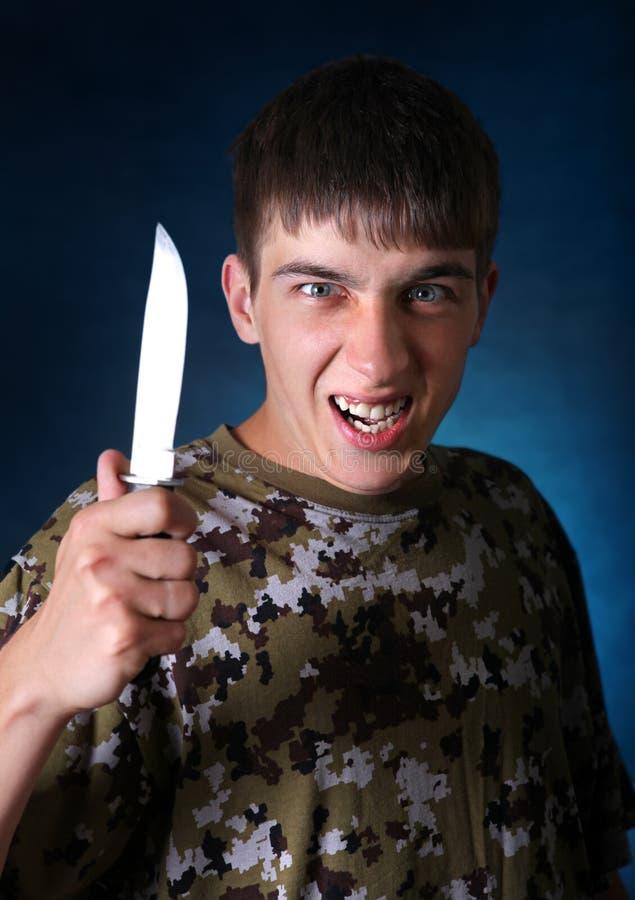 Сердитый подросток с ножом стоковое фото