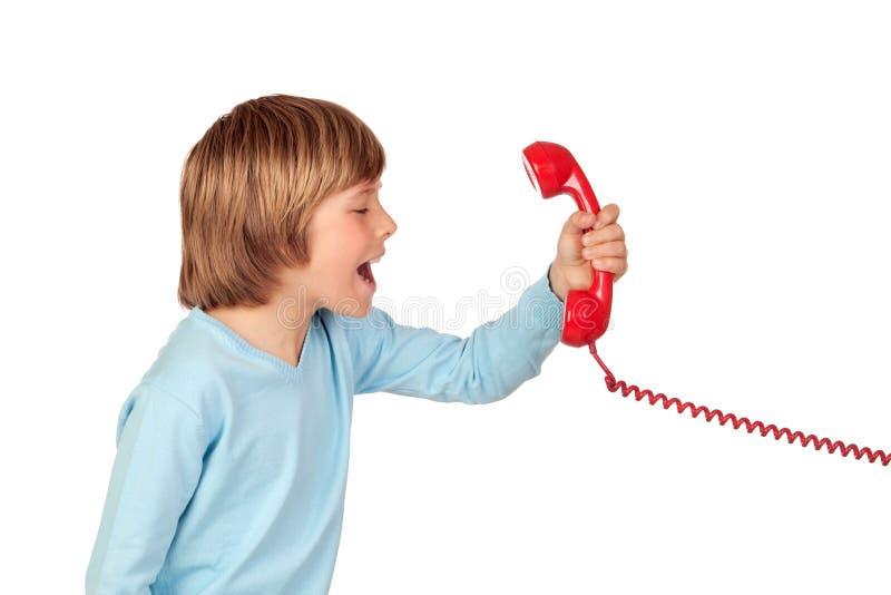 Сердитый ребенок крича на телефоне стоковое фото rf