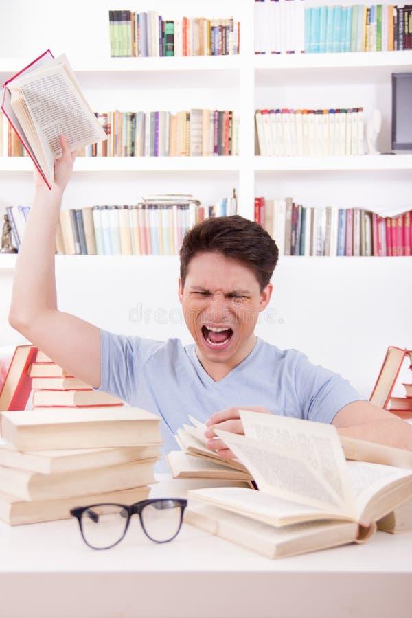 Сердитый студент окруженный книгами бросает книгу стоковые изображения