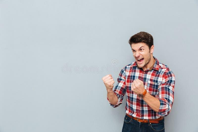 Сердитый сумашедший человек в рубашке шотландки показывая кулаки и кричать стоковые изображения rf