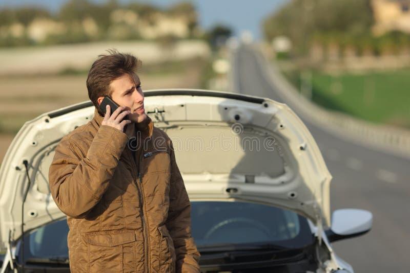 Сердитый человек вызывая помощь обочины для его автомобиля нервного расстройства стоковые изображения