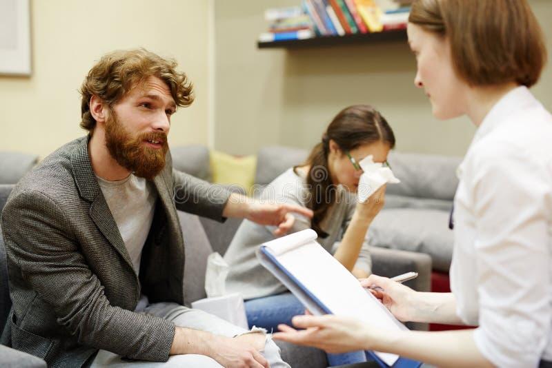Сердитый человек жалуясь о жене к психиатру стоковое изображение rf
