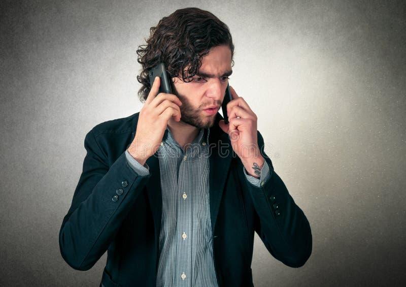 Сердитый человек на телефонах стоковая фотография