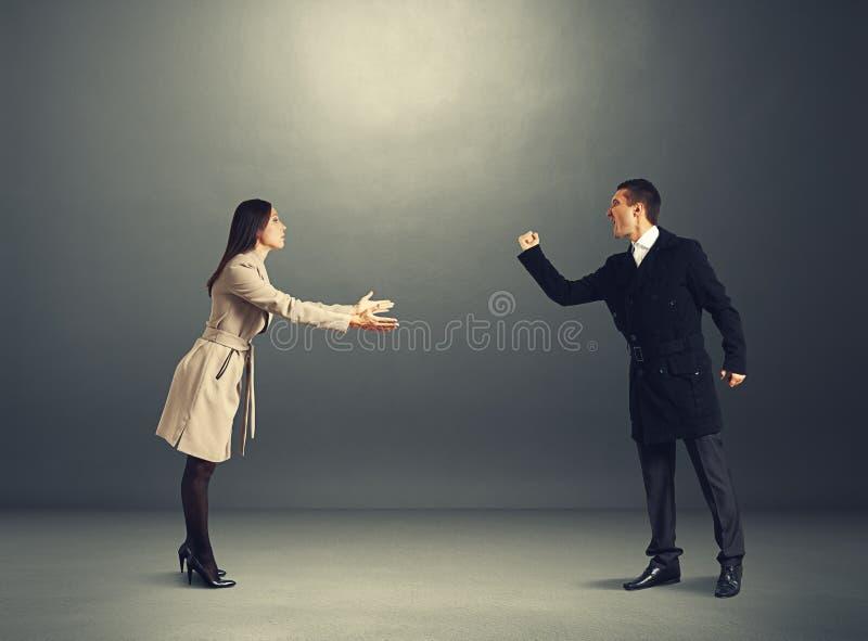 Сердитый человек на форах с молодой женщиной стоковое изображение rf