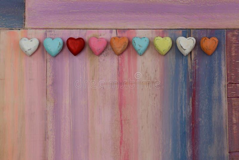 Сердца влюбленности красочные на покрашенной доске стоковое фото