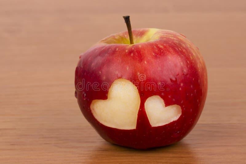 2 сердца на свежем яблоке, тема валентинки стоковое фото