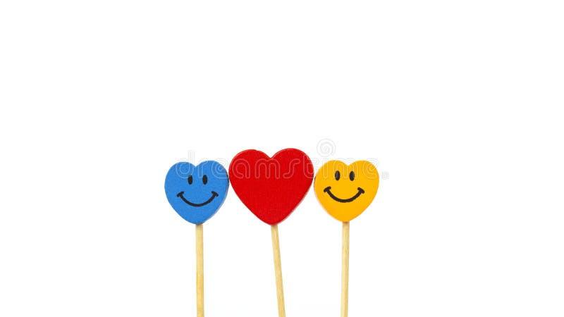 Сердце между 2 сторонами улыбки в середине белой предпосылки стоковая фотография