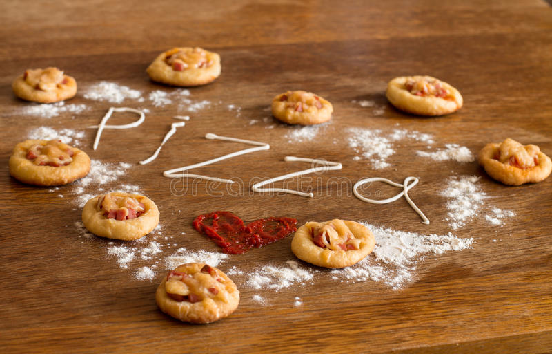Сердце мини пицц на деревянной таблице стоковая фотография