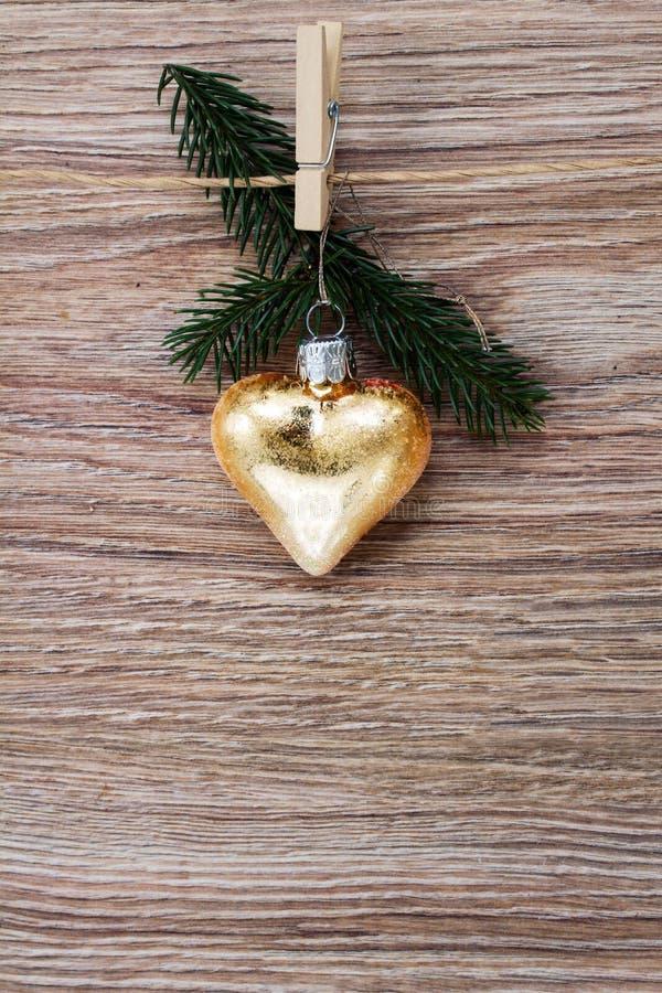 Сердце рождества золотое с зеленой хворостиной стоковые фото