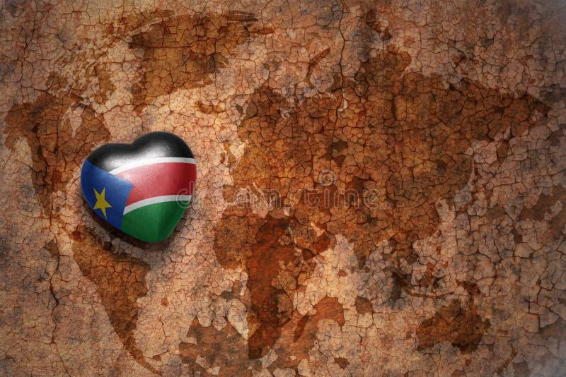 Сердце с национальным флагом южного Судана на винтажной предпосылке бумаги отказа карты мира стоковая фотография