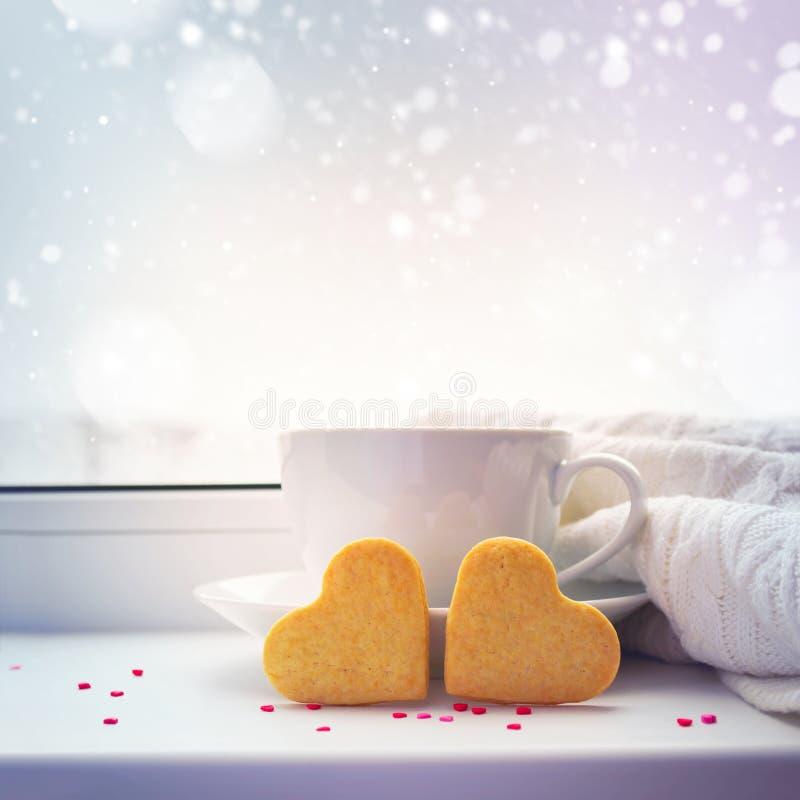 2 сердц-печенье, чашка кофе и одеяло против снежного ба стоковые изображения rf