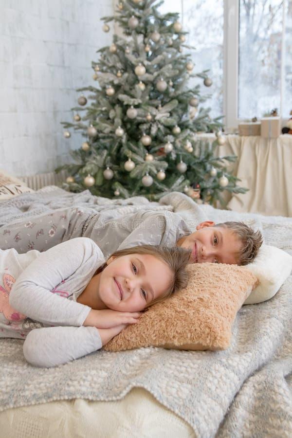 Сестра и брат лежа на кровати стоковые изображения