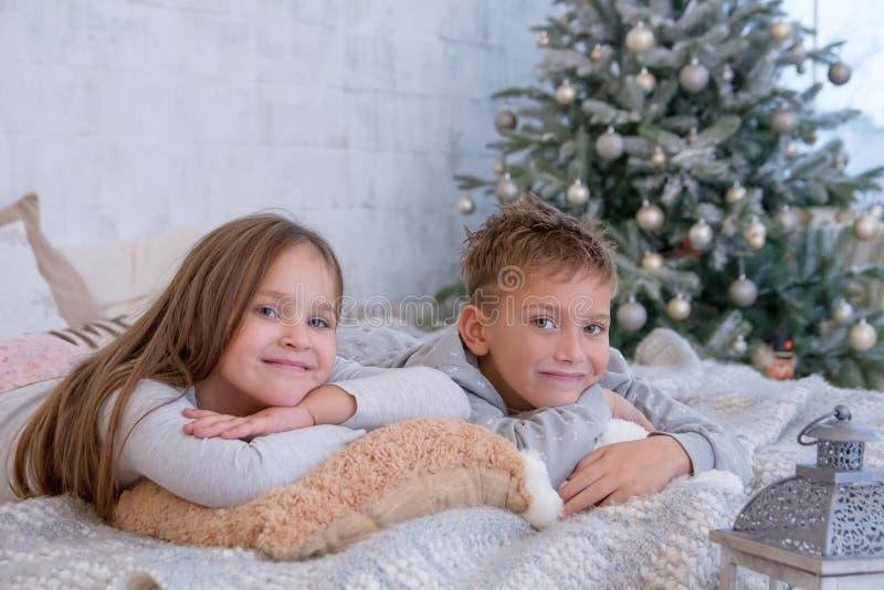 Сестра и брат лежа на кровати стоковые фотографии rf