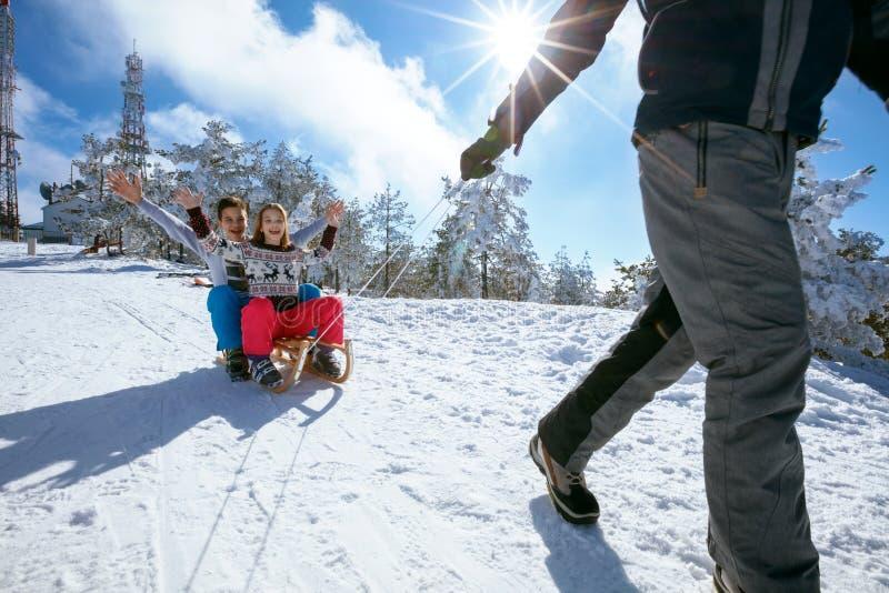 Сестра и брат на снеге sledding и наслаждаясь на солнечной зиме стоковое фото