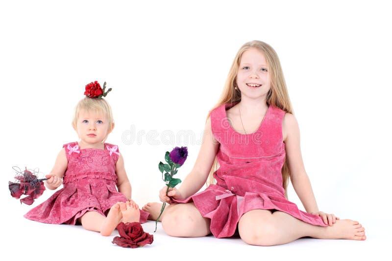2 сестры 9 год и 1-ти летних с игрушками стоковое фото