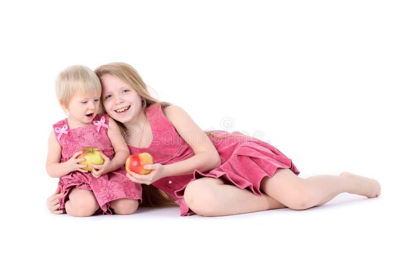 2 сестры 9 год и 1-ти летних с яблоком стоковое изображение