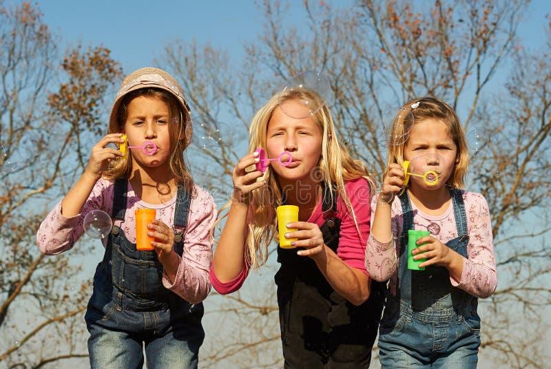 3 сестры детей девушек дуя пузыри с мылом в fie фермы стоковые изображения