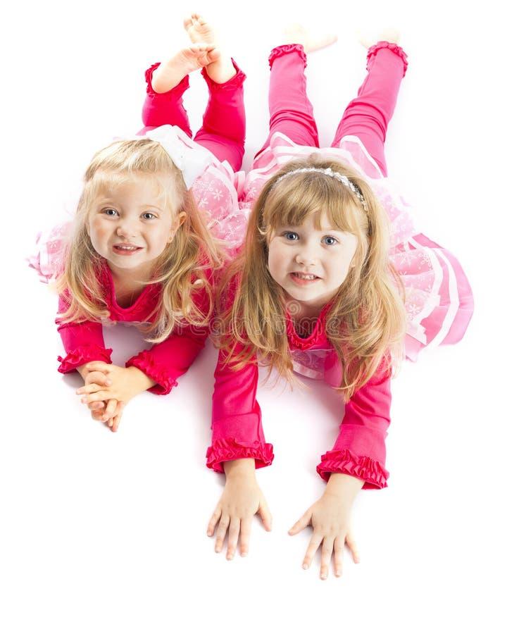 2 сестры кладя вниз с усмехаться стоковые фото