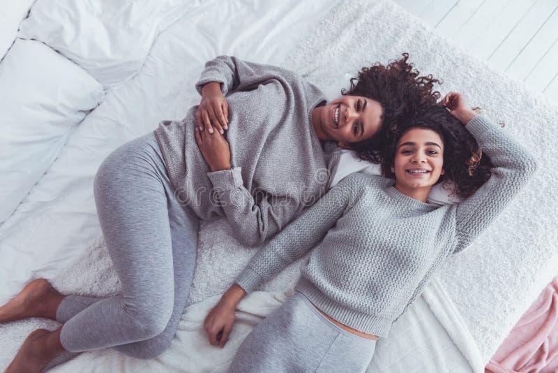 2 сестры нося такие же одежды чувствуя симпатичный стоковая фотография