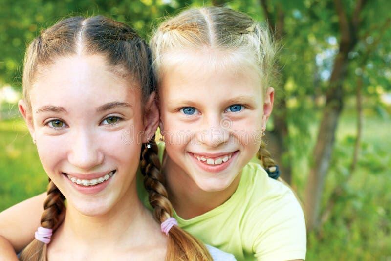 2 сестры обнимая и смотря камеру стоковое изображение
