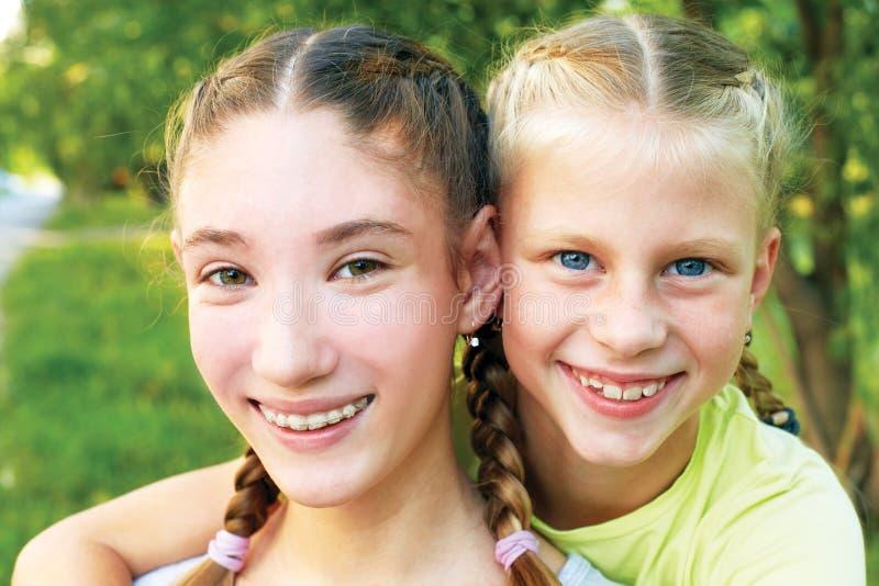 2 сестры обнимая и смотря камеру стоковое фото rf