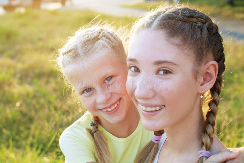 2 сестры обнимая и смотря камеру стоковая фотография