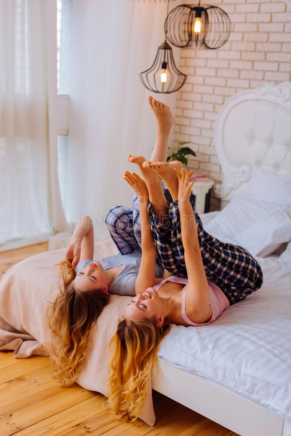 Сестры с пижамами курчавых светлых волос нося и охлаждать в кровати стоковые фото