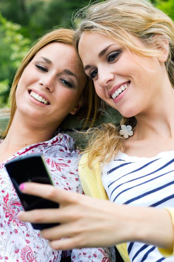Download 2 сестры с Smartphone на парке Стоковое Фото - изображение насчитывающей довольно, интернет: 33725098