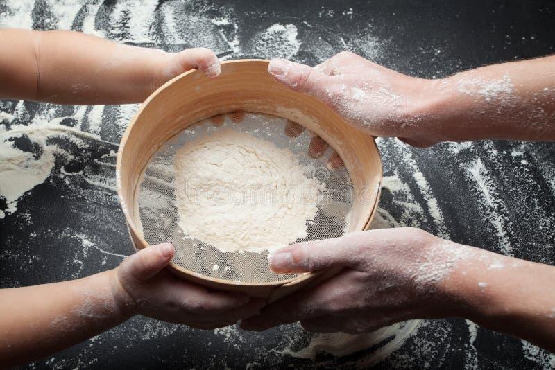Сетка для муки и руки женщины и ребенка Мама учит, что моя дочь засует муку и варит домодельные торты стоковое фото