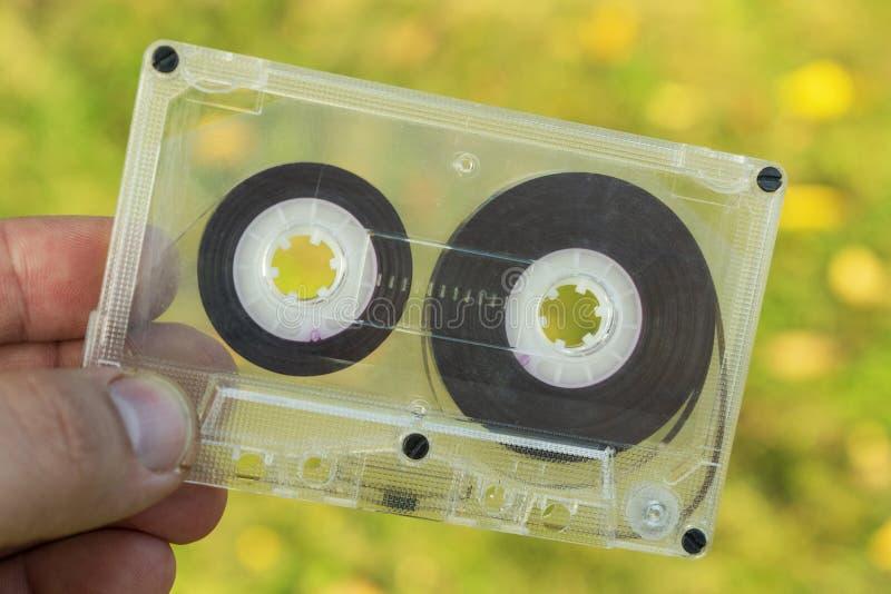 Сетноая-аналогов старая магнитофонная кассета в руке стоковое фото rf