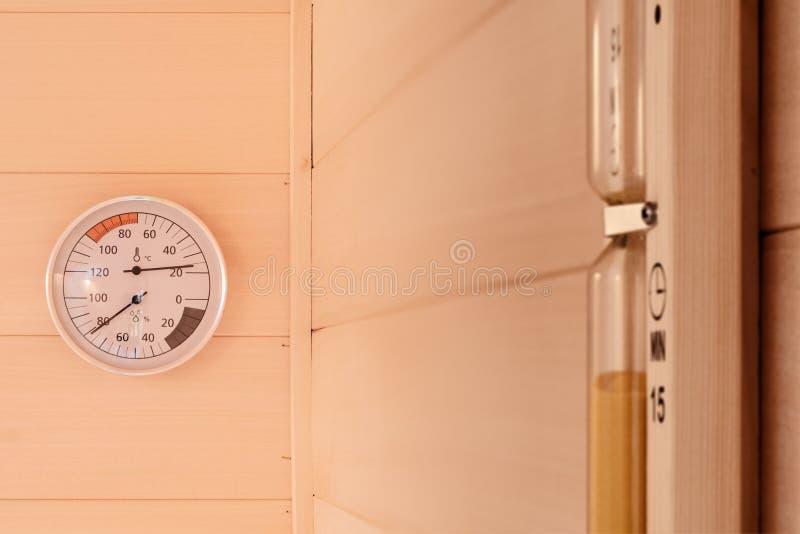 Сетноые-аналогов термометр и часы Детали от небольшой частной финской сауны стоковые фотографии rf