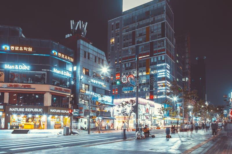 СЕУЛ, КОРЕЯ - 12-ОЕ АВГУСТА 2015: Серии молодые люди идя занятой главной улицей района на ноче - Сеула Sinchon, южного Kor стоковая фотография