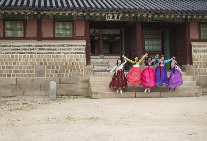 Сеул, Южная Корея - 4-ое сентября 2017: 5 корейских туристских женщин в традиционном Hanok одевают скакать от лестниц buildin стоковые фотографии rf