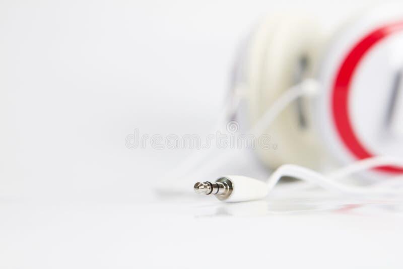 Селективный фокус на тональнозвуковой штепсельной вилке наушников на белой предпосылке стоковое фото rf