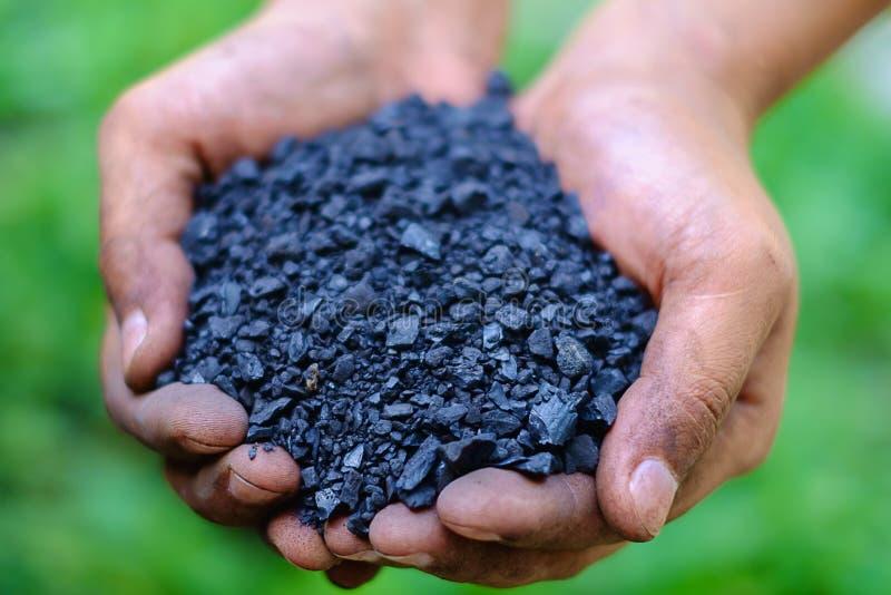 Селективный фокус определения размеров мелкого угля 0-10 mm в руках ` s работника стоковые фотографии rf
