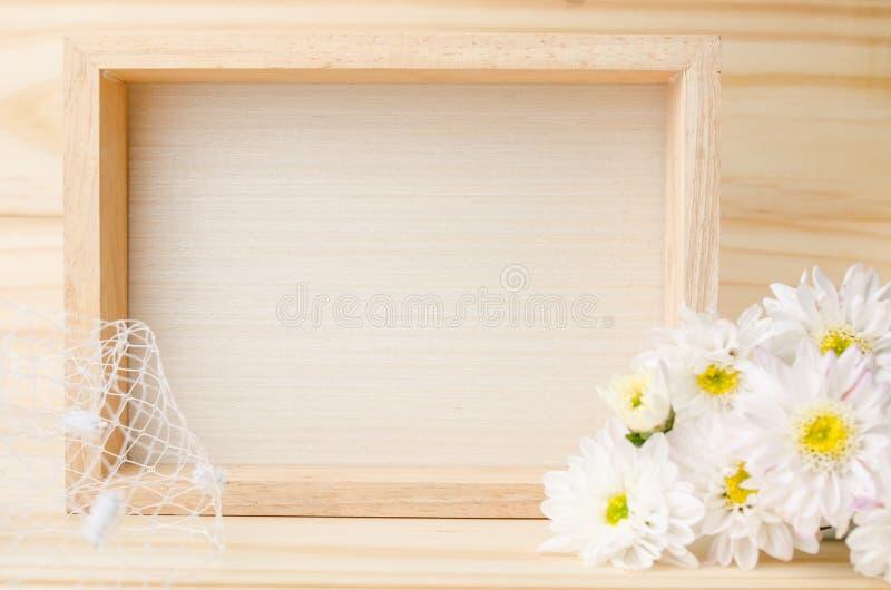 Селективный фокус рамки фото с цветками на деревянном столе стоковые фотографии rf