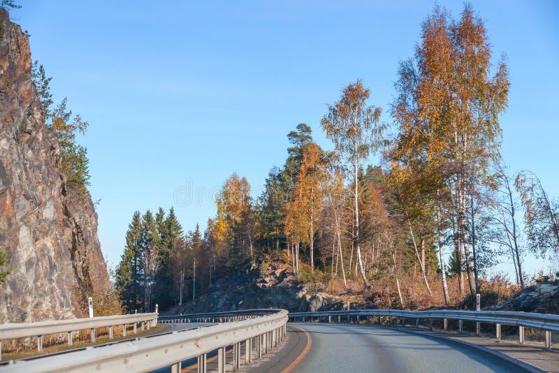 Сельская норвежская дорога идет около утесов стоковые изображения