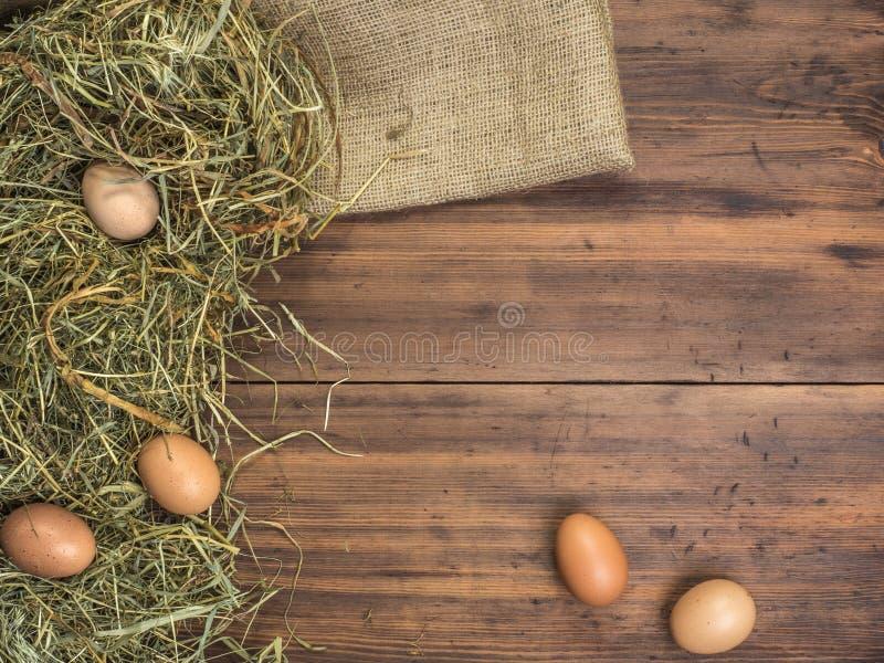 Сельская предпосылка eco с коричневыми яичками цыпленка, частью мешковины и соломой на предпосылке старых деревянных планок _ стоковые изображения rf