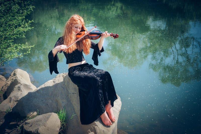 Сельская рыжеволосая девушка с скрипкой стоковые фотографии rf